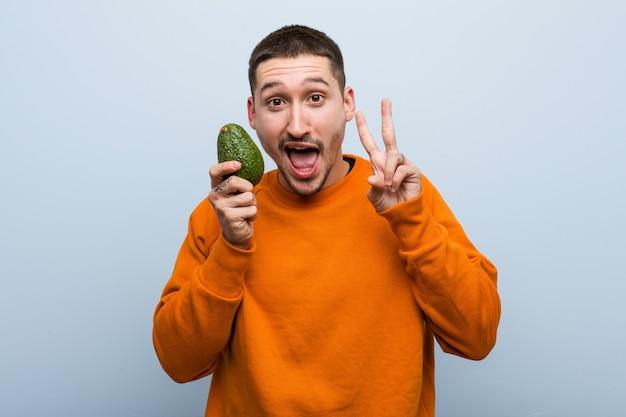 Junger kaukasischer mann, der eine avocado zeigt siegeszeichen und breit lächelt hält. Premium Fotos