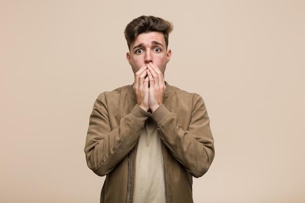 Junger kaukasischer mann, der eine braune jacke erschrocken und ängstlich trägt. Premium Fotos
