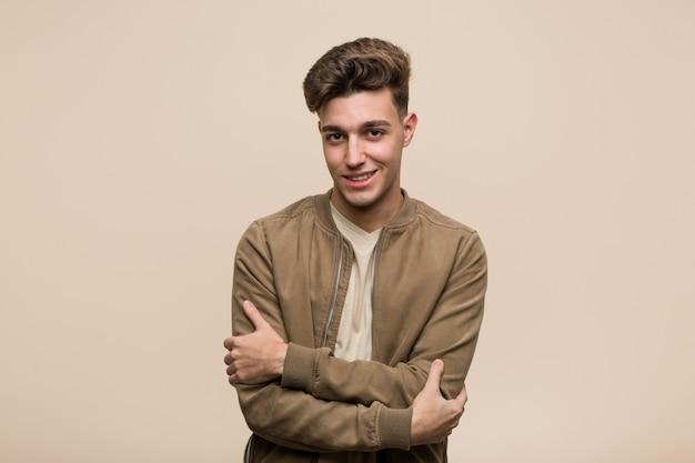 Junger kaukasischer mann, der eine braune jacke trägt, die überzeugt sich fühlt und arme mit entschlossenheit kreuzt. Premium Fotos