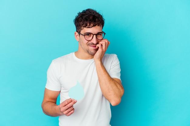 Junger kaukasischer mann, der weltwassertag feiert, isolierte beißende fingernägel, nervös und sehr ängstlich. Premium Fotos