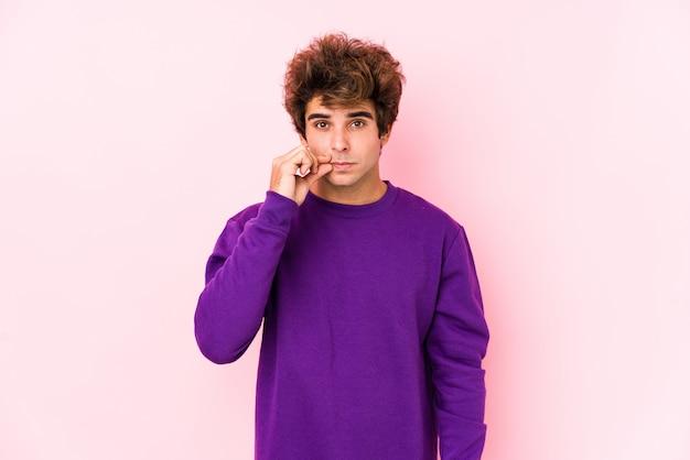 Junger kaukasischer mann gegen eine rosa wand lokalisiert mit den fingern auf den lippen, die ein geheimnis halten. Premium Fotos