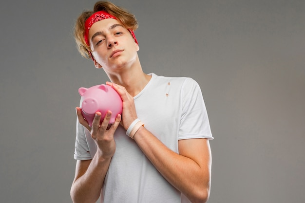 Junger kaukasischer mann in der roten sonnenbrille, weißes t-shirt mit rosa schweinespardose auf grauer wand Premium Fotos