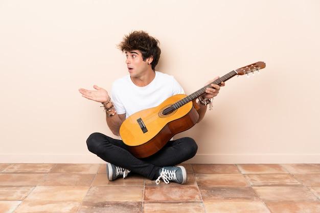 Junger kaukasischer mann mit einer gitarre, die auf dem boden mit überraschungsgesichtsausdruck sitzt Premium Fotos
