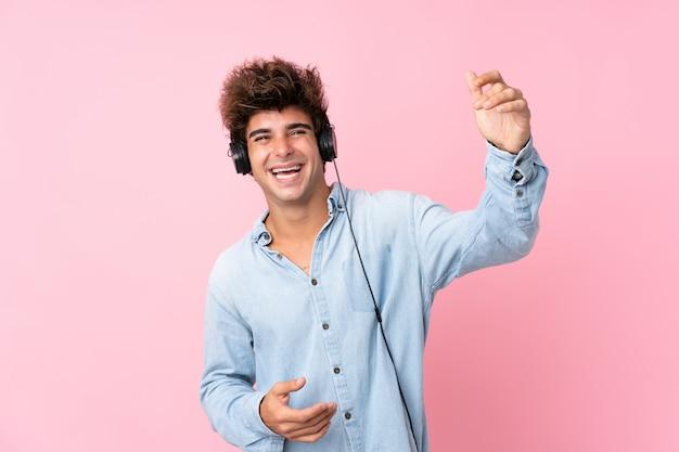 Junger kaukasischer mann über lokalisierter rosa wand unter verwendung des mobiles mit kopfhörern und tanzen Premium Fotos