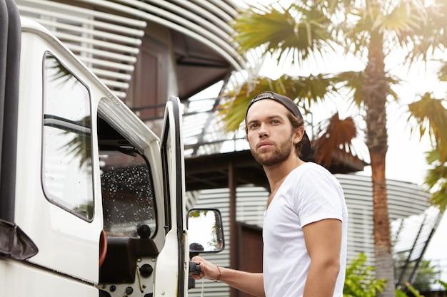 Junger kaukasischer reisender in hysterese, der in sein weißes geländewagen steigt, bereit, zum safari-rennen zu fahren Kostenlose Fotos