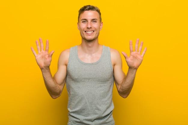 Junger kaukasischer sportmann, der nr. zehn mit den händen zeigt. Premium Fotos
