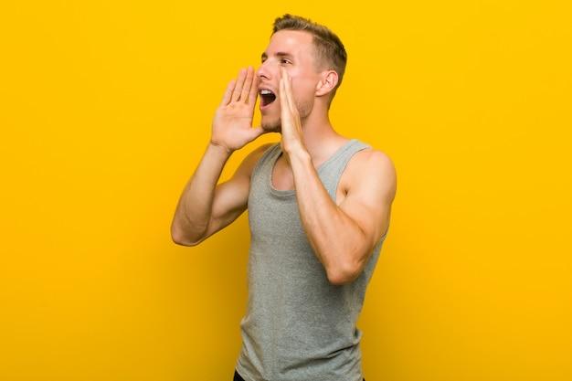Junger kaukasischer sportmann schreit laut, hält augen geöffnet und hände angespannt. Premium Fotos