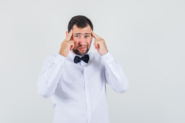 Junger kellner, der finger auf schläfen hält und kopfschmerzen in der vorderansicht des weißen hemdes hat. Kostenlose Fotos