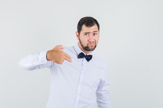 Junger kellner, der fingerpistolenzeichen macht, zeigte auf sich im weißen hemd und sah selbstbewusst aus. vorderansicht. Kostenlose Fotos