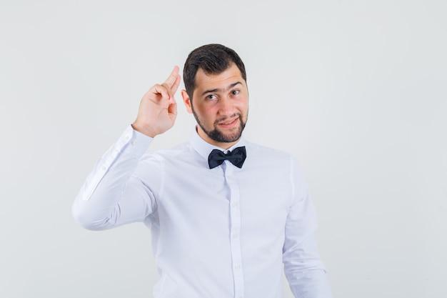 Junger kellner, der mit zwei fingern im weißen hemd gestikuliert und fröhlich aussieht. vorderansicht. Kostenlose Fotos