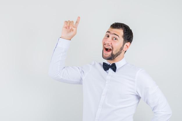 Junger kellner im weißen hemd, das finger oben zeigt und glückliche vorderansicht schaut. Kostenlose Fotos