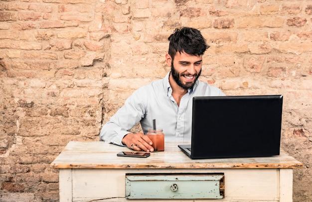 Junger kerl, der am weinleseschreibtisch mit laptop sitzt Premium Fotos