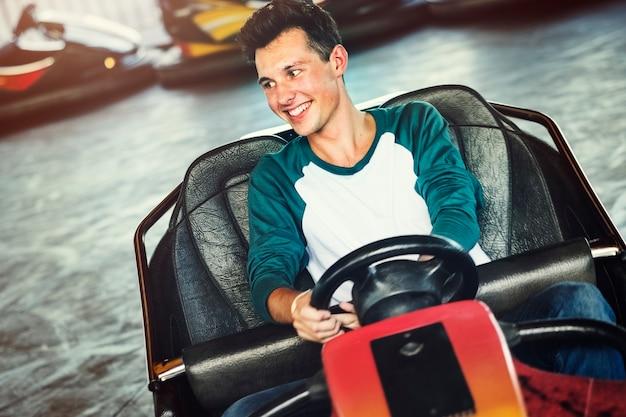 Junger kerl, der die stoßautos an einem vergnügungspark reitet Premium Fotos
