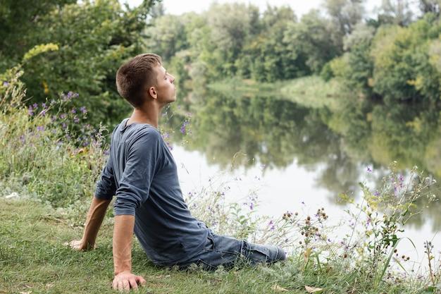 Junger kerl, der fern neben einem see schaut Kostenlose Fotos