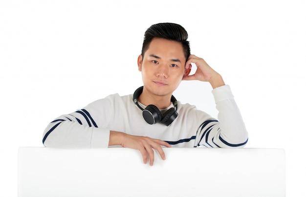 Junger kerl mit kopfhörer mit einem nachdenklichen blick, der auf der trennwand sich lehnt Kostenlose Fotos
