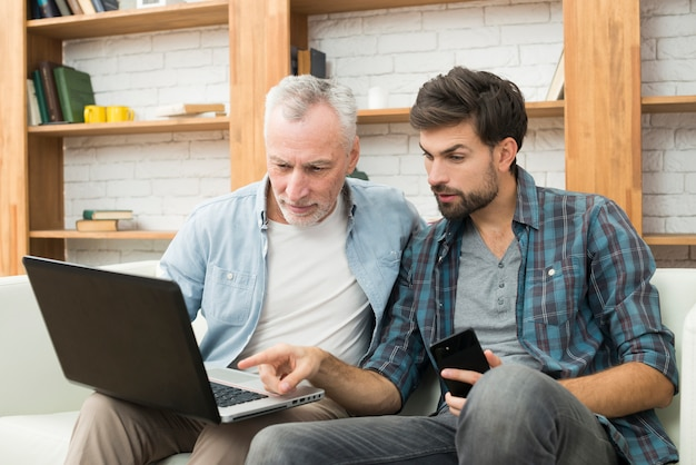 Junger kerl mit smartphone zeigend auf monitor des laptops auf beinen des gealterten mannes auf sofa Kostenlose Fotos