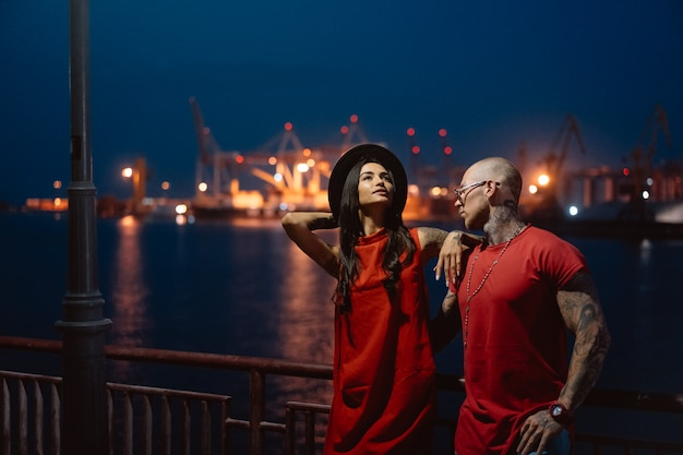 Junger kerl und schönes mädchen auf dem hintergrund des nachthafens Kostenlose Fotos