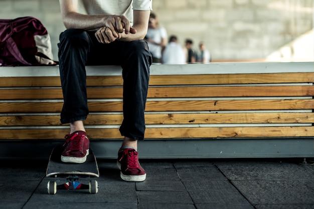 Junger klassischer skateboardfahrer, der im straßenlebensstil nah kühlt. Premium Fotos
