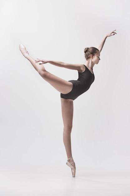 Junger klassischer tänzer, der auf weißem hintergrund tanzt. ballerina-projekt. Kostenlose Fotos