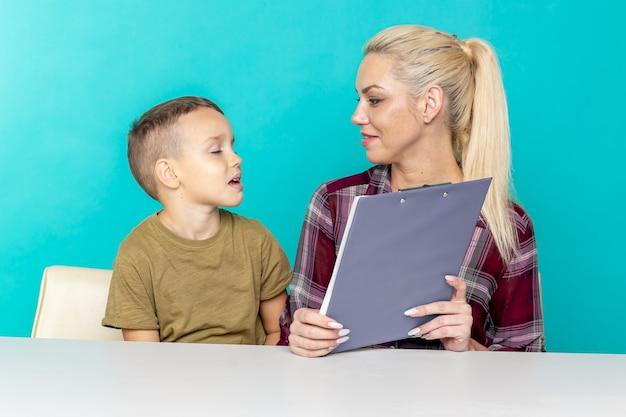 Junger kleiner schüler, der hausaufgaben mit mutter macht, zusammenarbeit in der familie, elternschaft. Premium Fotos