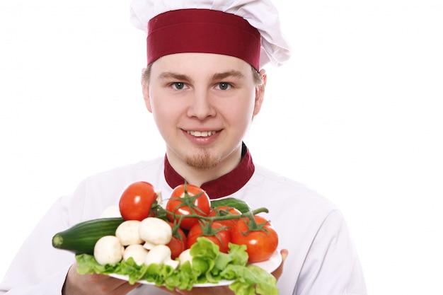 Junger koch, der teller mit gemüse hält Kostenlose Fotos