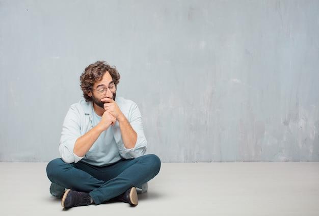 Junger kühler bärtiger mann, der auf dem boden sitzt. grunge wand hintergrund Premium Fotos