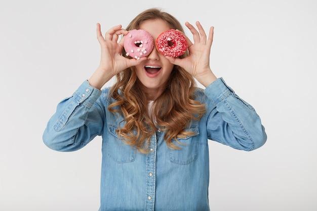 Junger kühler mann, der ein jeanshemd trägt, mit dem langen blonden gewellten haar, das durch donuts schaut und breit lächelt, lokalisiert über weißem hintergrund. Kostenlose Fotos