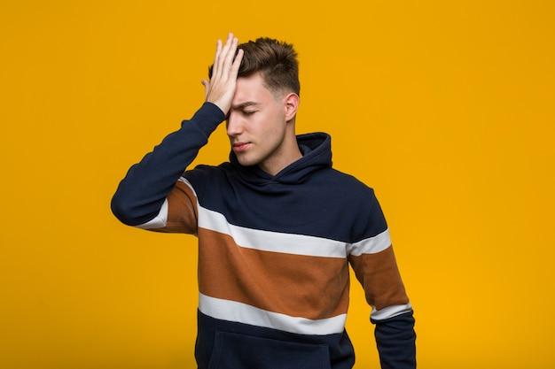 Junger kühler mann, der einen hoodie vergisst etwas trägt, stirn mit palme schlägt und augen schließt. Premium Fotos