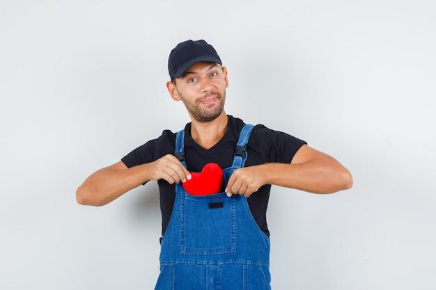 Junger lader in uniform, der rotes herz in seine tasche steckt und fröhliche vorderansicht schaut. Kostenlose Fotos