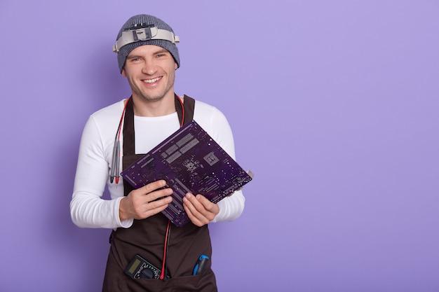 Junger lächelnder elektriker nach überprüfung der gebrauchstauglichkeit des motherboards Kostenlose Fotos