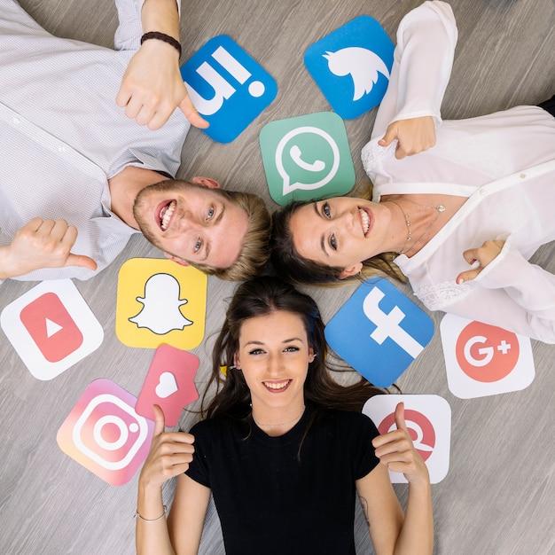 Junger lächelnder freund, der auf boden mit den social media-logos zeigt daumenzeichen liegt Kostenlose Fotos