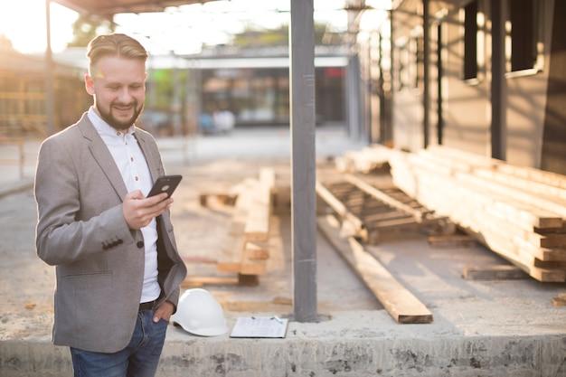 Junger lächelnder mann bei der anwendung des mobiltelefons an der baustelle Kostenlose Fotos