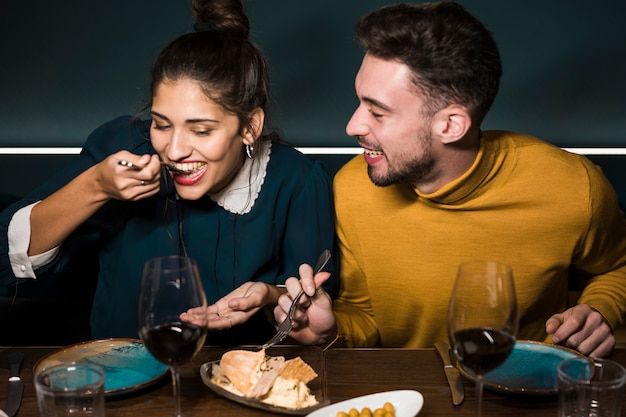 Junger lächelnder mann, der frau mit gabeln bei tisch käse im restaurant schmeckend betrachtet Kostenlose Fotos