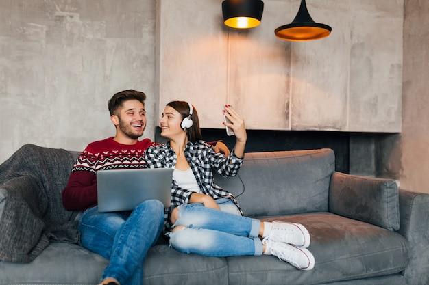 Junger lächelnder mann und frau, die zu hause im winter mit laptop sitzen, kopfhörer hören, paar auf freizeit zusammen, selfie-foto auf smartphone-kamera machend, glücklich, positiv, datierung, lachen Kostenlose Fotos