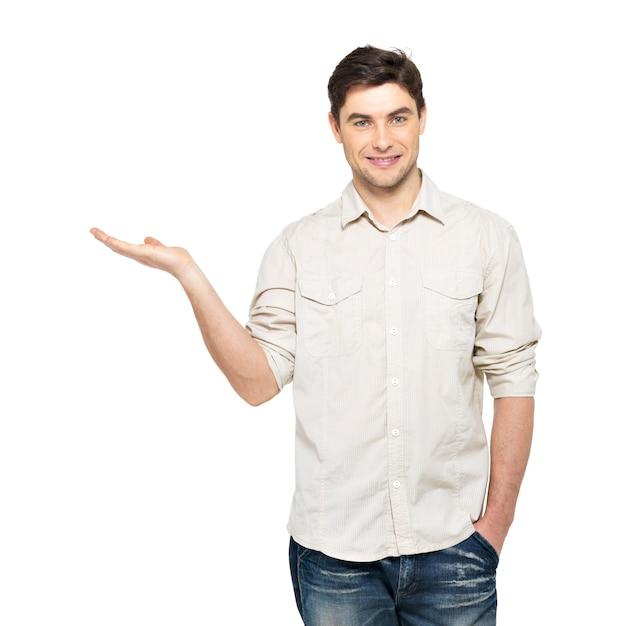 Junger lächelnder mann zeigt etwas auf handfläche lokalisiert auf weißer wand. Kostenlose Fotos