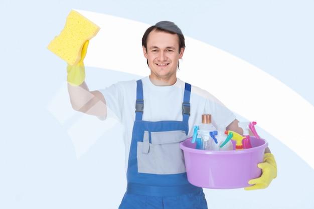 Junger lächelnder sauberer mann säubert fenster. Premium Fotos