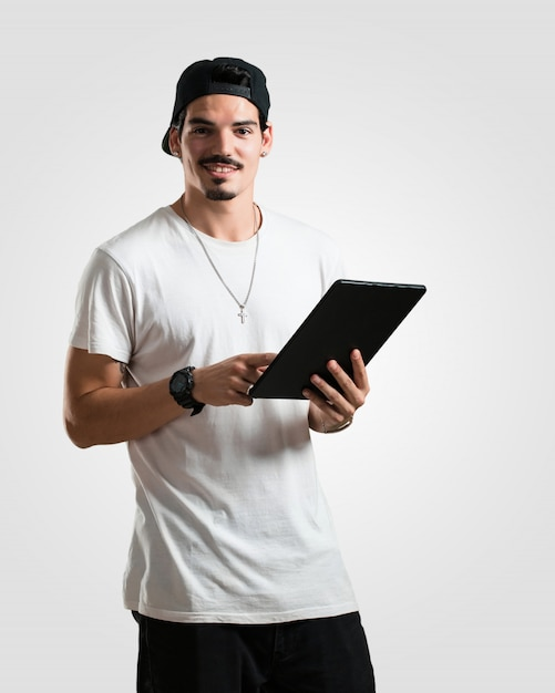 Junger lächelnder und überzeugter rappermann, eine tablette halten und verwenden, um das internet zu surfen und soziale netzwerke zu sehen, kommunikationskonzept Premium Fotos