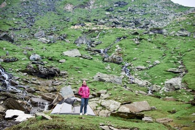 Junger lächelnder weiblicher tourist, der nahe zelt auf grüner felsenwiese in bergen in rumänien steht Premium Fotos