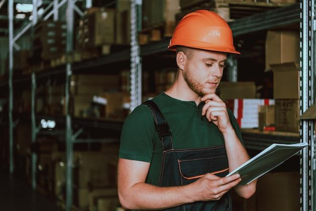 Junger lagerarbeiter im hardhat mit notizbuch Premium Fotos