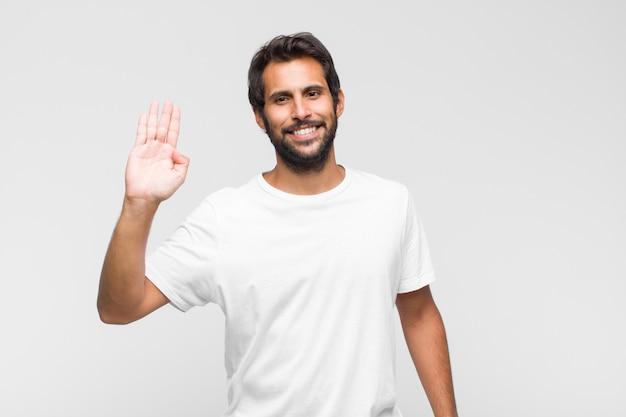 Junger lateinischer hübscher mann, der glücklich und fröhlich lächelt, hand winkt, sie begrüßt und begrüßt oder sich verabschiedet Premium Fotos