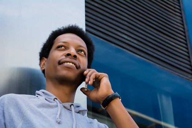 Junger lateinischer mann, der draußen am handy spricht. Premium Fotos