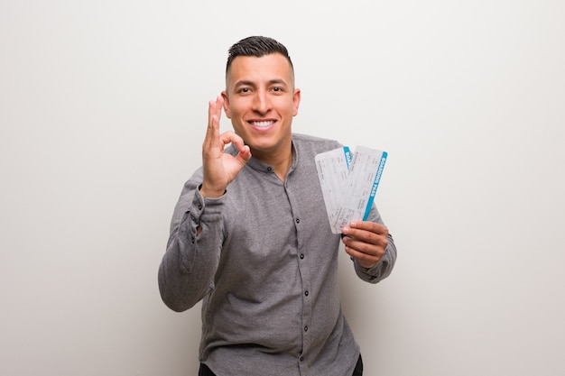 Junger lateinischer mann, halten flugtickets nett und überzeugt, okaygeste tuend Premium Fotos