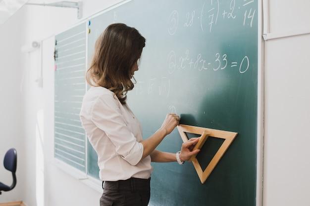 Junger lehrer oder schüler zeichnen dreieck auf einer tafel mit formel Premium Fotos