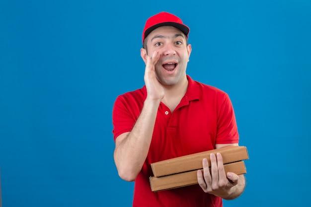 Junger lieferbote im roten poloshirt und in der kappe, die pizzaschachteln halten, die namen schreien, der jemanden mit hand nahe mund sucht, der fröhlich über isolierte blaue wand lächelt Kostenlose Fotos