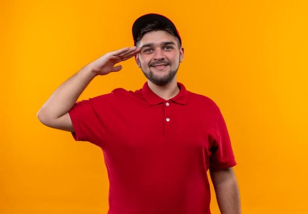 Junger lieferbote in der roten uniform und in der kappe, die zuversichtlich salutierend suchen Kostenlose Fotos