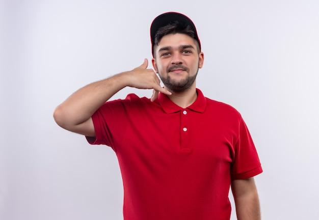 Junger lieferjunge in roter uniform und lächelnd zuversichtlich machen, rufen sie mich geste Kostenlose Fotos