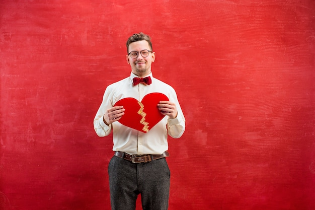 Junger lustiger mann mit abstraktem gebrochenem und geklebtem herzen auf rotem studiohintergrund. Kostenlose Fotos