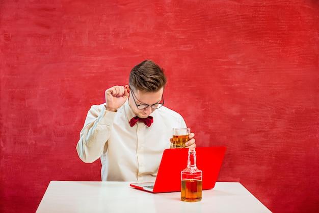 Junger lustiger mann mit cognac, der mit laptop am valentinstag auf rotem studiohintergrund sitzt. Kostenlose Fotos