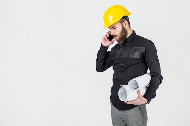 Junger männlicher architekt, der die blaupausen sprechen am handy hält Kostenlose Fotos