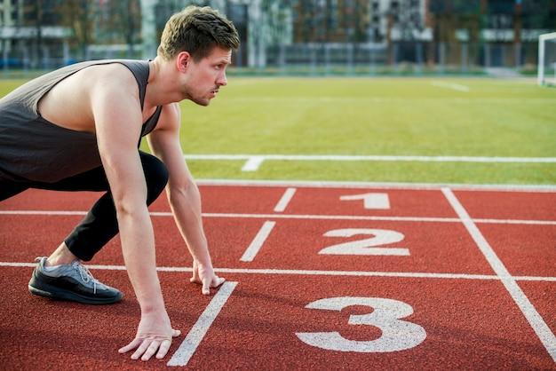 Junger männlicher athlet bereit zu laufen, stellung an der startlinie nehmend Kostenlose Fotos